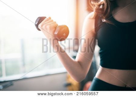 Hand Of Sports Woman Lifting Dumbbell For Weight Training Near Window By Right Hand For Pumping Bice