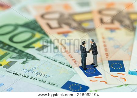 Miniature figure agreement concept with businessmen shaking hand standing on Euro flag on pile of Euro banknotes as Euro economy discussion or Brexit negotiation concept.