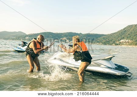 Senior happy couple having playful fun at jet ski on beach island hopping tour - Active elderly travel concept around the world with retired people riding water scooter jetski - Bright vintage filter