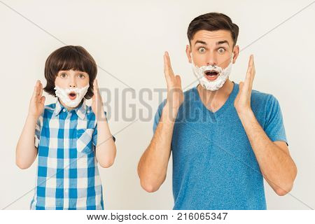 The father shows his son how to shave in the bathroom. The boy smeared with foam for shaving. Both of them were very lucky.