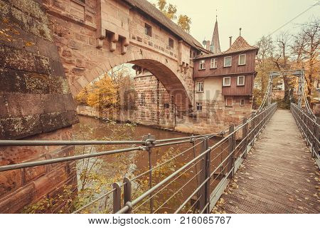Stone houses and suspension bridge across the river in the historic city of Nuremberg with historical walls. Old Bavaria of Germany.