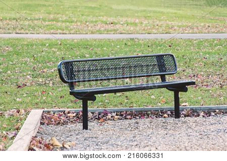 a park bench in an empty park on a fall morning