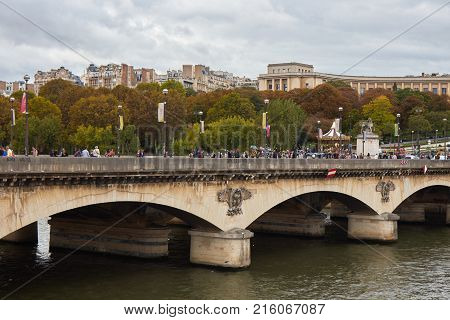 Paris, France - October 2 2017: People are walking on the Pont de l'ena bridge next to the Eiffel tower in the autumn day.