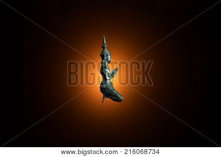 small ancient buddha statue on dark background