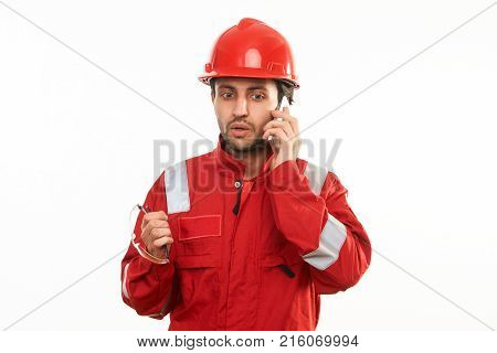 Young builder worker in red hardhat helmet and workwear uniform speaks by mobile phone isolated on white background with copy space, close-up portrait
