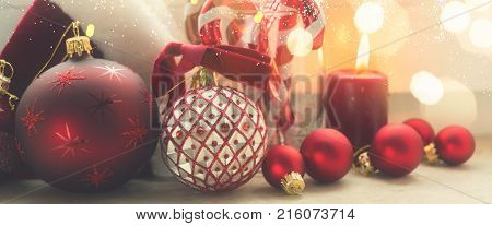 Christmas styled scene with burning candle and christmas decorations on winter windowsill, retro toned