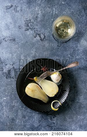 Traditional dessert sliced poached pears in white wine served in black plate with syrup, ice cream, lemon zest and glass of white wine over blue texture background. Top view with space