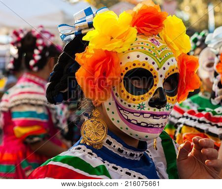 Girl wearing colorful skull mask and paper flowers for Dia de Los Muertos/Day of the Dead celebration in San Antonio, TX