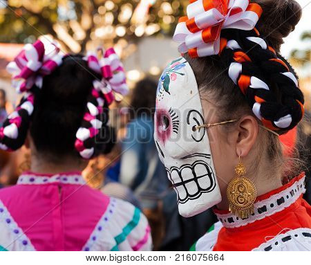 Profile of woman colorful skull mask and hair ribbons for Dia de Los Muertos/Day of the Dead
