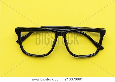 modern eye glasses on yellow background.glasses lie . Black orange glasses . Office workplace with glasses on wood table. Glasses with orange rim. Orange Case for storage points.