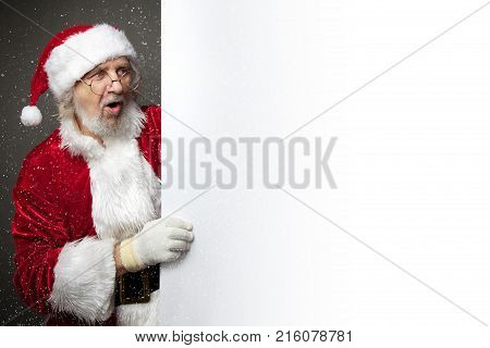 Surprised Santa Claus showing something on a white wall