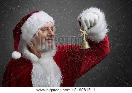 Jingle bells. Santa Claus holding metal bell in his hand and against dark grey background