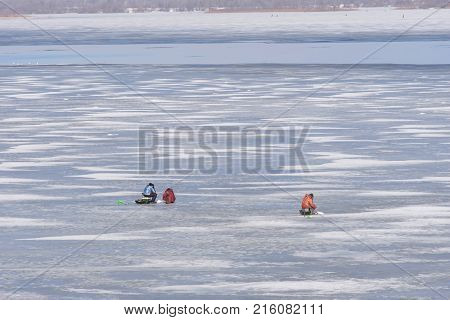 Late fishing on the Oka ice. Ice melts and there is open water on it. Fearless stupid fishermen enjoy fishing at weak spring ice..