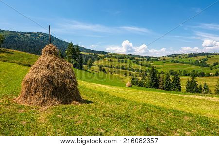 Haystack On A Grassy Rural Field In Mountains