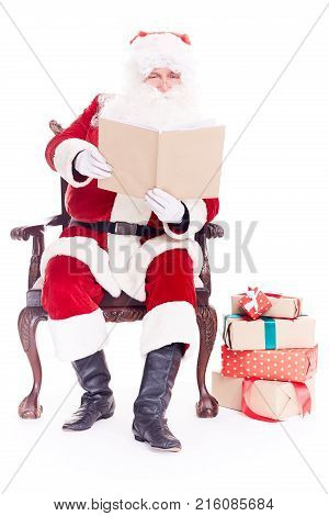 Portrait of santa Claus sitting in chair and reading a book on white background