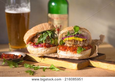 Double Burger on the board on wooden background. Huge double burger on a wooden board on a wooden background. Really huge burger with another burger close