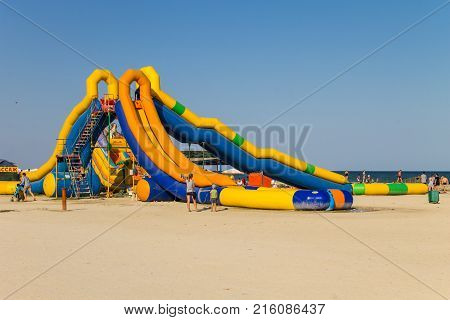 Genichesk, Ukraine - August 24, 2017: Inflatable water slide on beach of Azov sea. Favorite vacation spot of children and adults