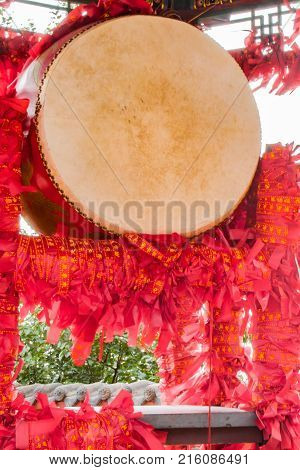 Close up of a prosperity drum with symbolic wish ribbons tied around the stand.