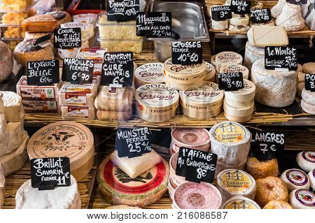 Paris France - Jule 09 2017: A large selection of different french and italian cheeses on the counter of a small store at the Aligre Market (Marche d'Aligre) in the Bastille district.