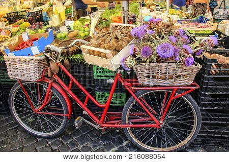 Bicycle with baskets of chestnuts and artichokes on the market of Campo di Fiori Rome Italy
