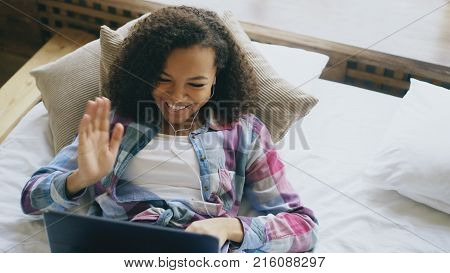Cheerful mixed race girl having video chat with friends using laptop camera while lying on bed at home