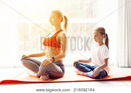 Mother and daughter are engaged in yoga in sportswear. They are in a bright room with panoramic windows. They are sitting in accomplished pose.