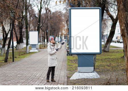 The Young Woman Points To An Empty Billboard On The Alley In The Park