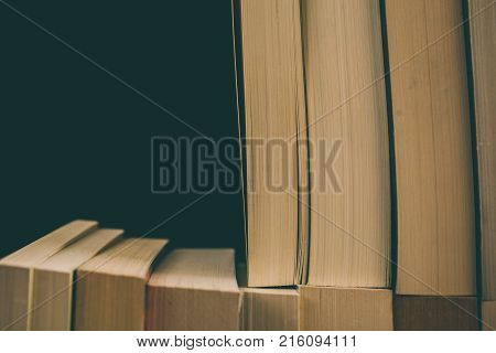 Books background. Old vintage books background. Education and knowledge, learn, study and wisdom concept. Stack of old books. Old books on a shelf, stacked old books in vintage style.