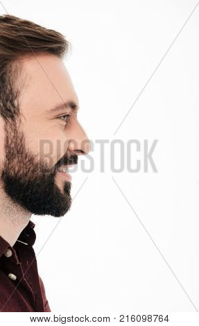 Side view half face portrait of a smiling bearded man laughing and looking away at copy space isolated over white background