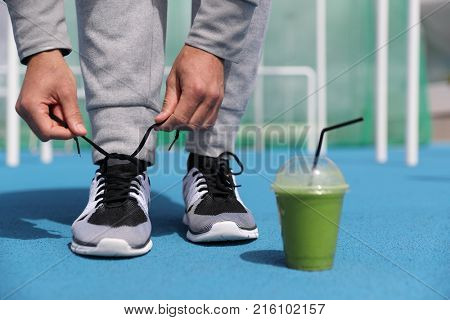 Gym fitness man getting ready tying running shoes with green smoothie detox beverage. Closeup of running trainers with plastic cup of breakfast vegetable juice. Sport active lifestyle.