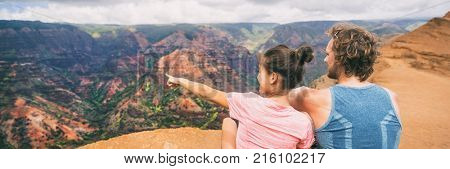 People hiking in Hawaii banner hikers pointing at Kauai mountains. happy hiker couple healthy lifestyle outdoors looking at Waimea canyon view. Young couple in nature in Kauai, Hawaii, USA.