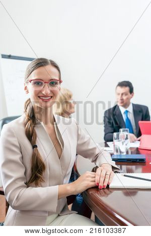 Portrait of a beautiful business woman looking at camera with a can-do attitude while sitting down at a round table, during a decision-making meeting with the board of directors