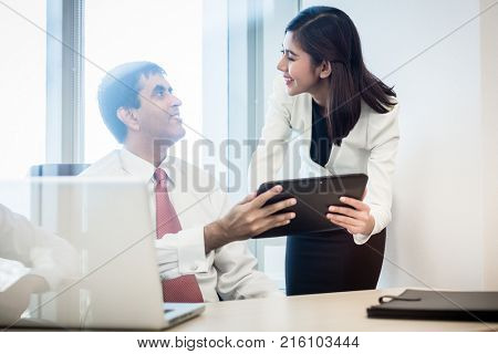 Indian businessman and Indonesian secretary in office checking days schedule