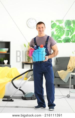Young man with cleaning supplies at home