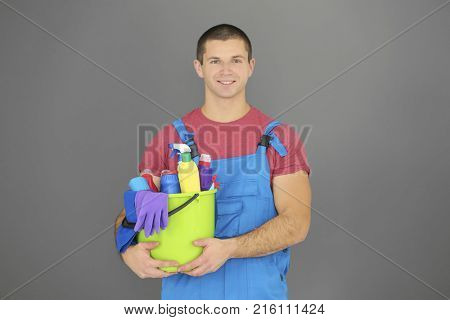 Young man with cleaning supplies on grey background
