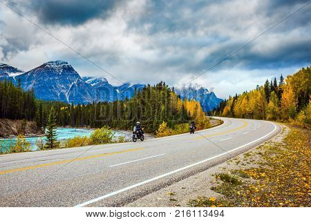 Motorcyclists driving on the road. The concept of active tourism. The astonishing nature of the Rockies of Canada. The road 93