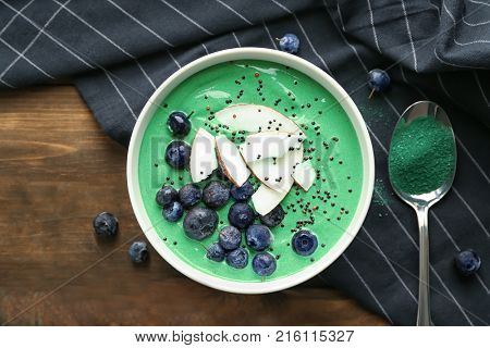 Bowl with yummy spirulina smoothie on table. Healthy vegan food concept