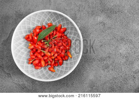 Bowl with fresh goji berries on table