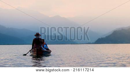 Tourists on old small boat sailing on the Phewa lake on the sunset, Nepal