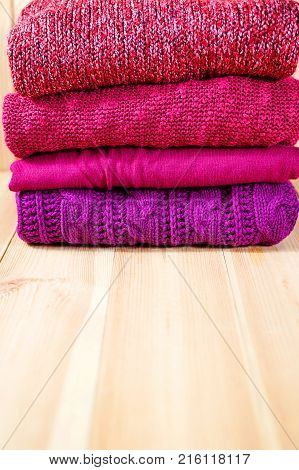 Stack Of Warm Pink, Purple And Violet Cozy Sweaters