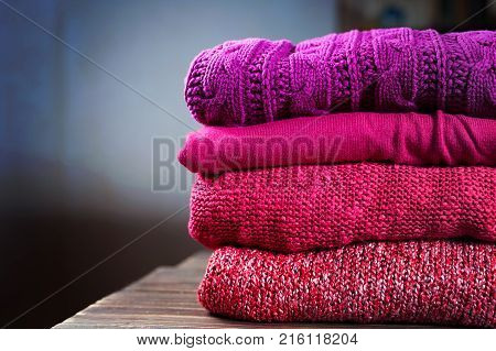 Stack Of Warm Knitting Clothing Lying On A Wooden Table