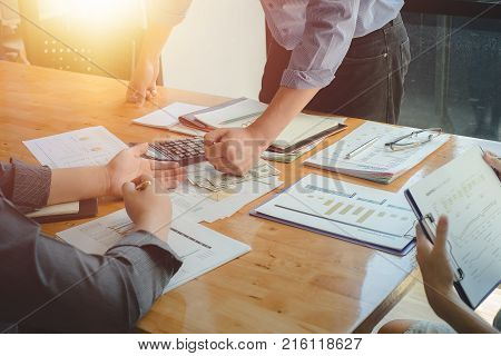Business team discussing analysis chart with one man hand banging fist over money on desk problems stress.Defrauded cheated investor demanding money back.Business and finance concept Vintage effect.
