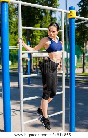 Young girl in a bright blue sport bra and black leggings leaning against the horizontal bar on the sport playground. Photo of an athlete girl with a beautiful sports body