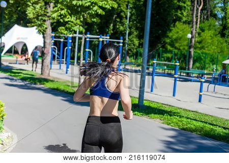 Young sportive woman in a bright blue sport bra and black leggings running along the path near sport playground. Photo of an athlete girl with a beautiful sports body, back view