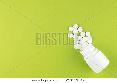 Close Up White Pill Bottle With Spilled Out Pills On Pear Yellow Background With Copy Space. Focus O