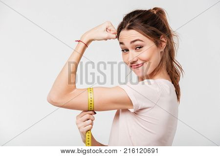 Portrait of a smiling happy girl flexing biceps with a measuring tape around her arm isolated over white background