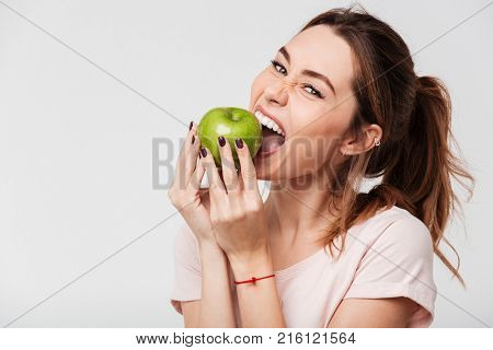 Close up of a hungry funny girl biting an apple isolated over white background