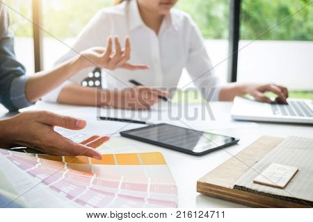 Two young women interior design or graphic designer working on project of architecture drawing with work tools and color swatches colour chart in digital tablet at workplace.