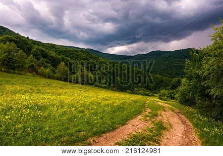 Grassy Field On Hillside In Stormy Weather