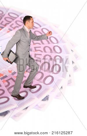 Businessman in grey suit runs on circle of euro in perspective